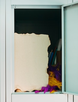 Burnt paper and feather boa in open locker
