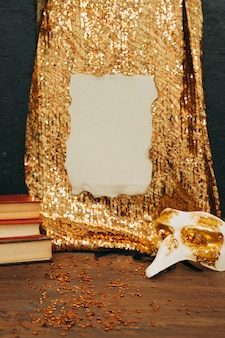 Burnt paper on golden sequin textile with carnival mask on wooden table
