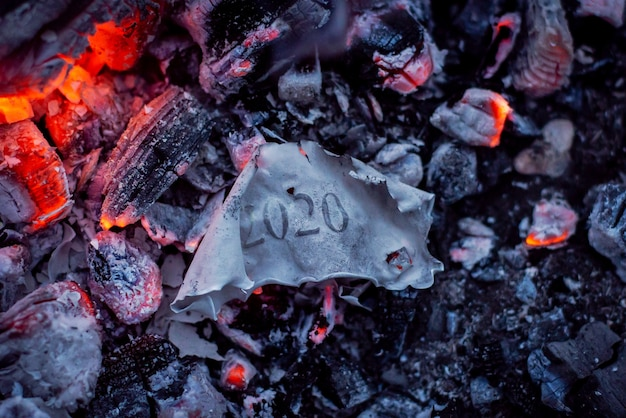 Burnt paper with inscription 2020 in ashes of the fire