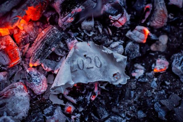 Обгоревшая бумага с надписью 2020 в пепле огня