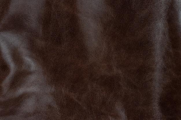 焦げたアンバーチョコレートの質感の滑らかな革の表面の背景、小さな穀物