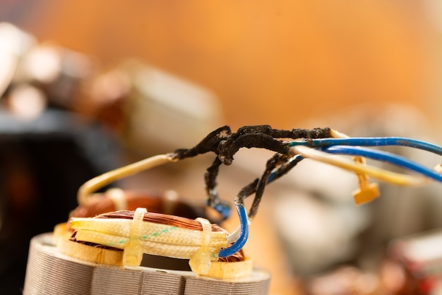 Burnt wires on the parts of an electrical appliance, drills on a wooden table in a repair shop. power tool repair