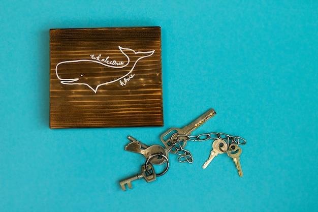 파란색 배경에 칠해진 고래와 열쇠가 있는 탄 나무 수제 표지판 whalecom home. 집에 오신 것을 환영합니다. 집에 있어