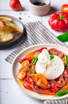구운 토마토, 후추, 적양파, 신선한 바질을 곁들인 부라타 치즈