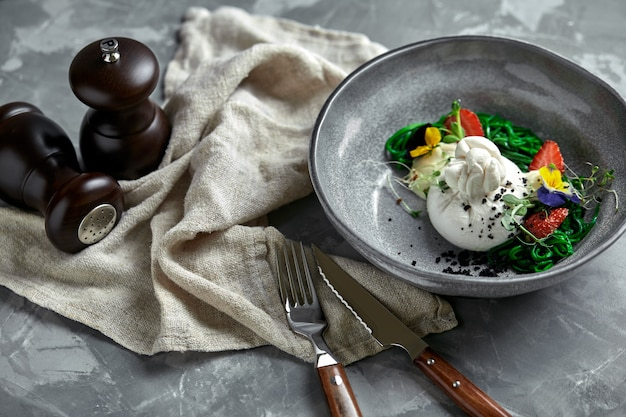 Burrata salad with strawberries and seaweed, on a gray