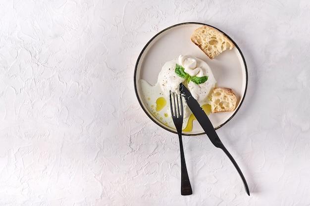 흰색 접시에 바질 치아바타 빵과 올리브 오일을 곁들인 부라타, 검은 칼과 포크 위쪽 전망