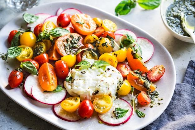 수제 페스토를 곁들인 다채로운 체리 토마토 샐러드를 곁들인 부라타