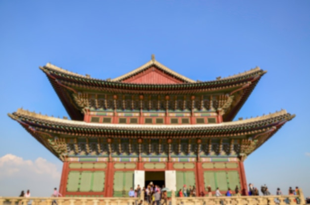 Burred picture of tourists examine the main throne hall at gyeongbokgung palace