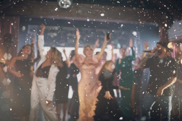 ステージにマイクを持ち、前景に輝きを放つ、バリのある歌手とファン