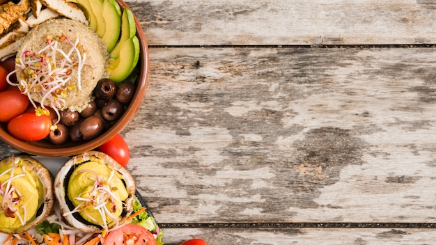 Burrito bowl with chicken; tomato; sprouts; olives and avocado slices in bowl with salad on wooden textured backdrop