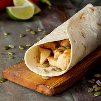 Burrito on cutting board near cardamom seeds