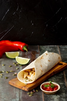 Burrito on cutting board near peppers, lime and tomato sauce against black background