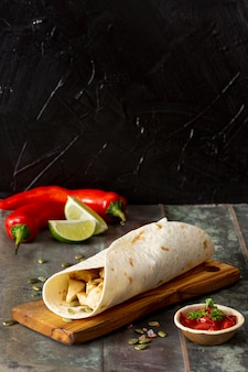 Burrito on cutting board near peppers, lime and tomato sauce