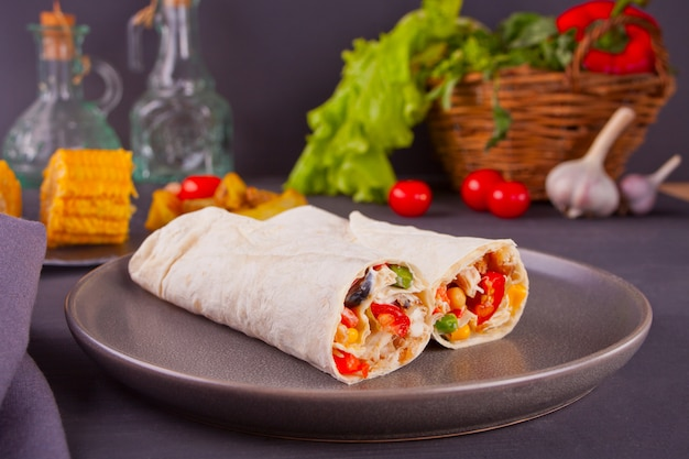 Burrito rolls with vegetables on black table and vegetables, cherry tomatoes and garlic at background