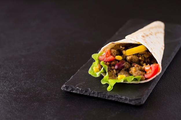 Буррито с говядиной, курицей, лаймом, перцем и овощами на каменной доске. серый фон. мексиканская еда.