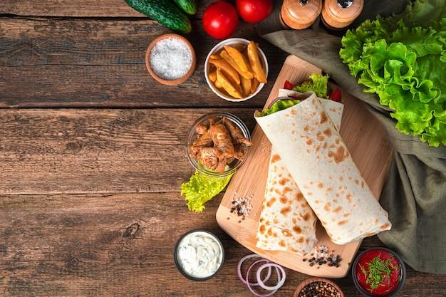 Буррито с курицей и овощами на коричневой стене со свежими ингредиентами. быстрое питание. вид сверху, копия пространства.