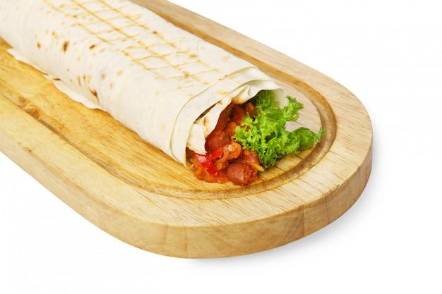 Burrito with chili con carne at wooden desk