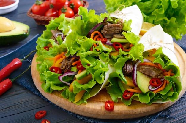 暗い背景の木のまな板にみじん切りの肉、アボカド、野菜、唐辛子とブリトー。トルティーヤのぬいぐるみ。伝統的なメキシコの前菜。