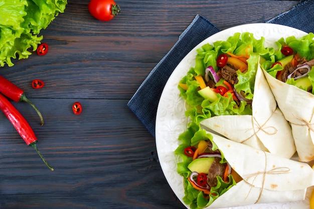 みじん切りの肉、アボカド、野菜、暗い背景の木の皿に唐辛子とブリトー。トルティーヤのぬいぐるみ。伝統的なメキシコの前菜。上面図。