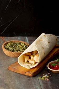 Burrito on wooden board near tomato sauce and cardamom
