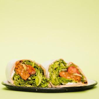 Буррито на тарелке на мятно-зеленом фоне