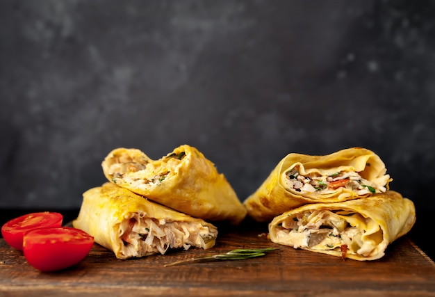 Burrito wraps with chicken and vegetables , against a background of concrete, mexican shawarma