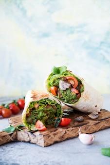 ブリトーは野菜とソースのペストで包み、野菜、マッシュルーム、ペストソースでロールします。