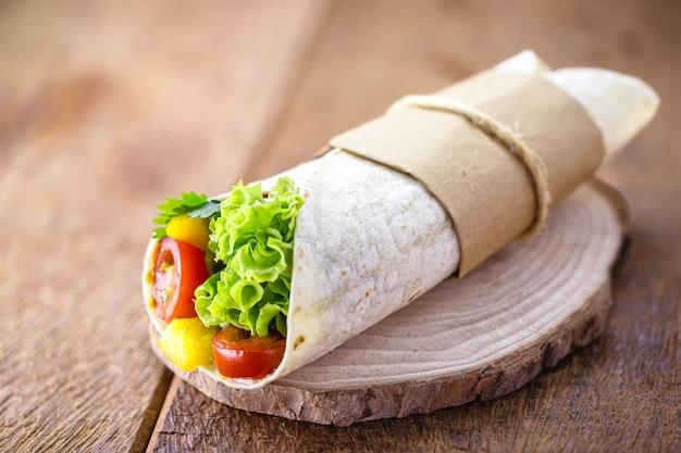 きのこ、ピーマン、キャベツ、その他の野菜のグリルで包んだブリトーまたはビーガンラップ