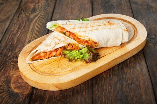Burritos with chili con carne at wooden desk