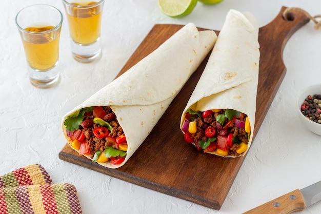 Буррито с мясом, фасолью, кукурузой, помидорами, луком и перцем чили. мексиканская еда. рецепт приготовления.