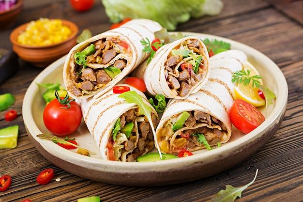 Обертывания буррито с говядиной и овощами на деревянном столе. буррито из говядины, мексиканская еда. мексиканская кухня