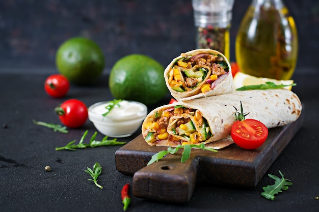 Burritos обертывается говядиной и овощами на черном фоне. говядина буррито, мексиканская еда.