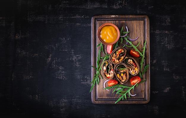 Обертывания буррито с говядиной и овощами на темном деревянном фоне. буррито из говядины, мексиканская кухня. вид сверху, вверху