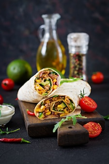 Burritos wraps with beef and vegetables on  black background. beef burrito, mexican food.