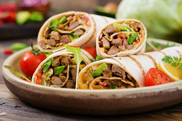 Burritos wraps with beef and vegetables on wood. beef burrito , mexican food. healthy food background. mexican cuisine.