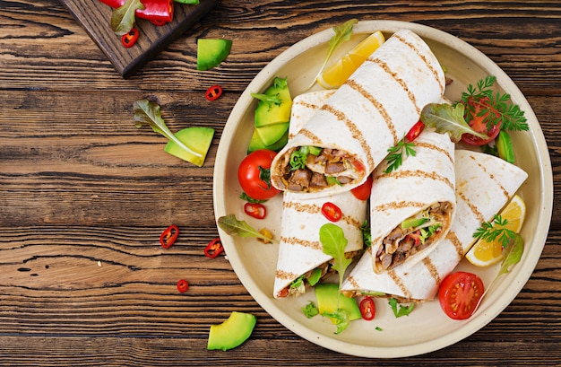 Burritos wraps with beef and vegetables on a wooden table. beef burrito , mexican food. mexican cuisine.top view.