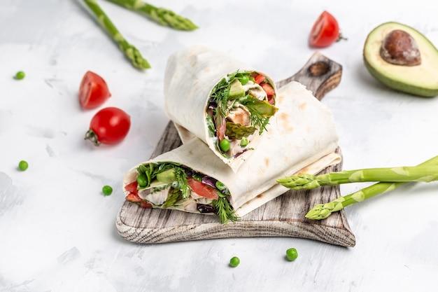 ブリトーは鶏肉と野菜のアスパラガス、アボカド、トマト、エンドウ豆、チーズで包みます