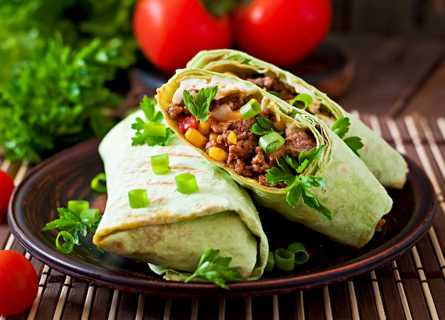 Burritos wraps with minced beef and vegetables on a wooden surface