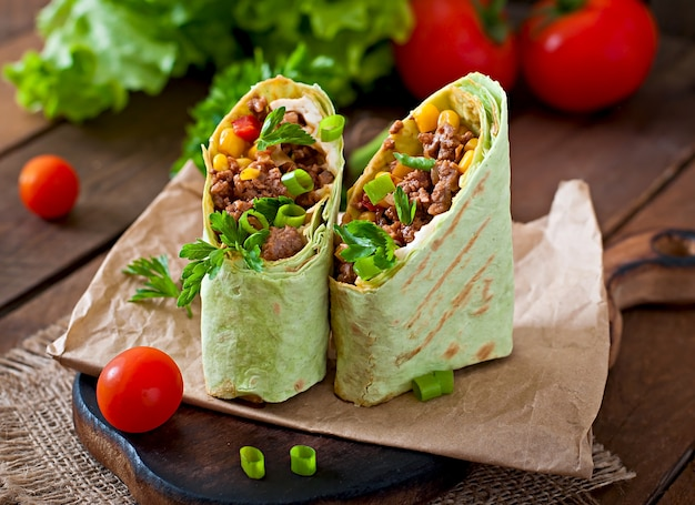 Burritos wraps with minced beef and vegetables on a wooden