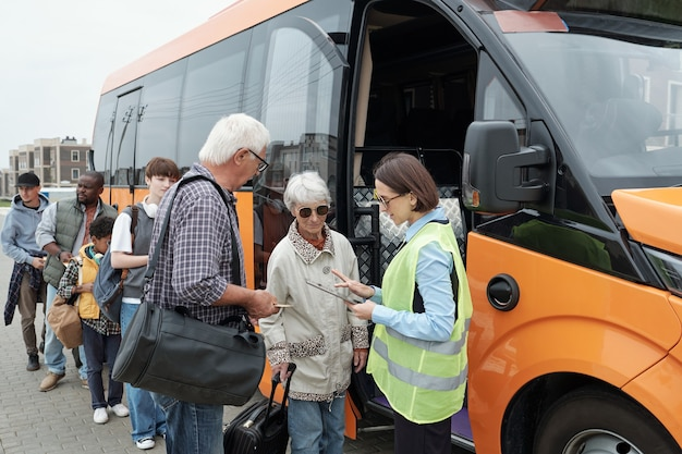 탑승 전 승객의 티켓을 확인하는 버스 기사