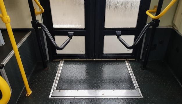 黄色のハンドル付きバスドア、内部ビュー。市内の現代の公共交通機関のドアを開閉するためのメカニズム。