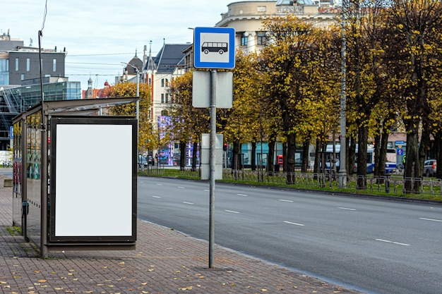Bus stop in city with empty white mock up banner for advertising, clear public information board in urban setting in autumn day
