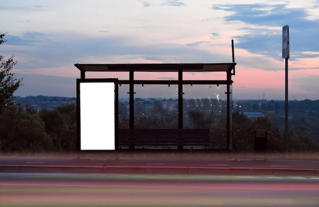 透明な公共情報を宣伝するための空白の白いモックアップバナーが付いている市内のバス停