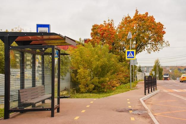秋の日に空の看板がモックアップされたバス停人のいないガラスのバス停は誰もいない秋