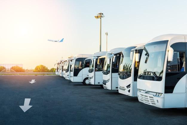 일출 때 공항 주차장에서 버스. 휴일, 여행, 관광 및 휴가 개념입니다.