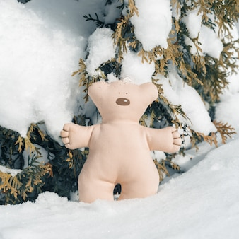 Bush covered with snow with textile christmas bear toy