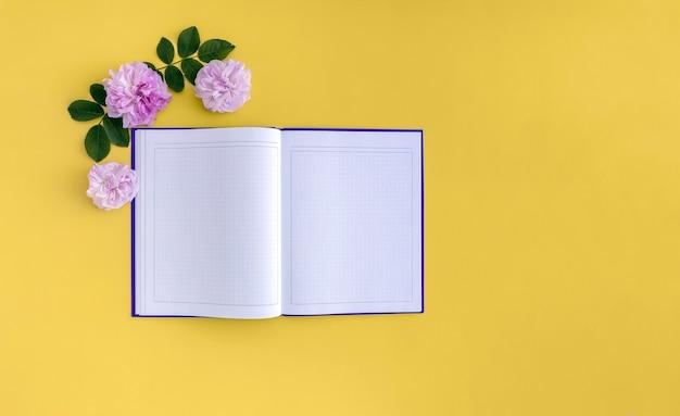 Куст розовых цветов и тетрадь