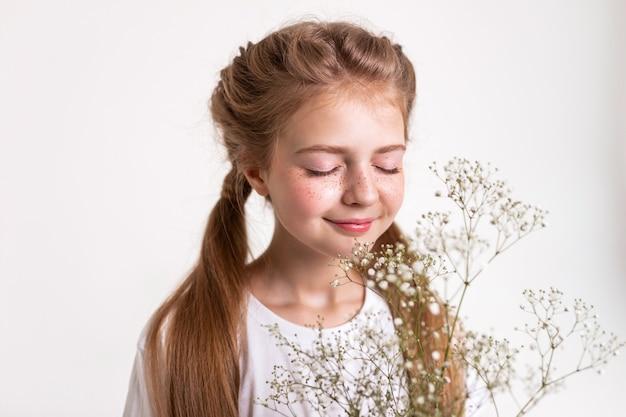 Кустовые белые цветы. вдохновленная спокойная маленькая девочка, пахнущая ароматом цветов в руках