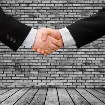 モダンなインテリアの背景を持つビジネスマン握手