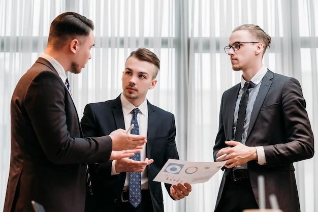 ビジネスチームミーティング。オフィスで仕事のことを話し合う男性